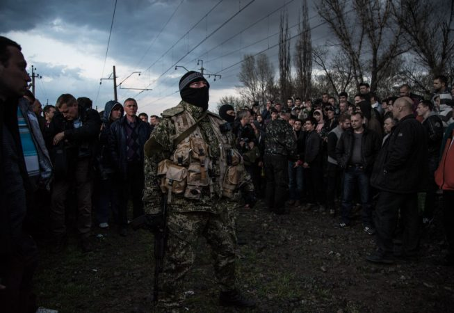 Masked pro-Russian fighters supported by the crowd disarm Ukrainian Army convoy near Pchelkino village, East Ukraine