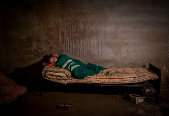 A girl who was brought to see a doctor is asleep in the basement of Novoazovsk ambulance station during the shelling