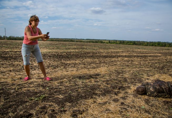 A local woman takes a picture of the dead Ukrainian soldier in the field near the town of Komsomolskoye, Donetsk region.