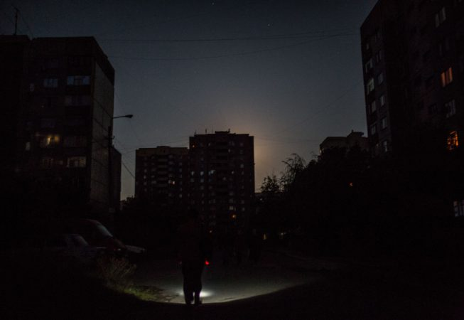 A local is walking with a torchlight in Luhansk. The home of 500k people, Luhansk had to electricity for 2 months during the summer