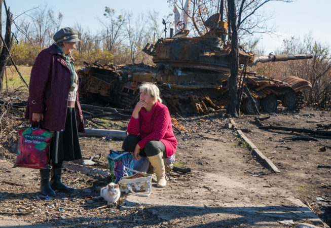 Locals are waiting for a bus by a tank wreck in Novosvetlovka village, Luhansk region. The village was nearly destroyed during the heavy fighting between insurgents and government troops