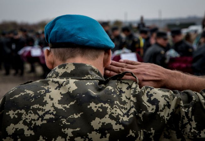 A marine veteran salutes at the funeral ceremony of unidentified Ukrainian servicemen in Dnipropetrovsk
