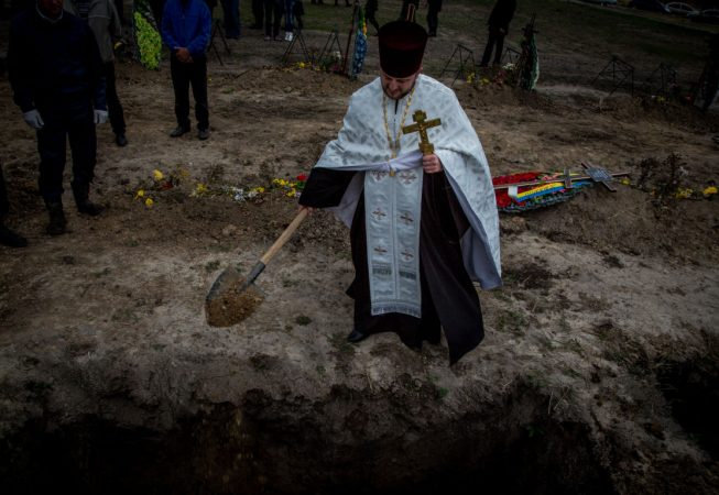 A priest is throwing dust at the grave of unknown Ukrainian soldier during mass burial ceremony in Dnipropetrovsk