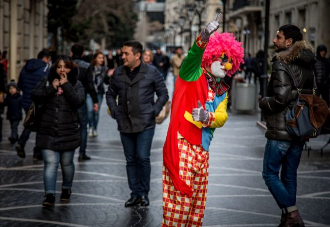 A clown tries to attract customers for a shop in central Baku.