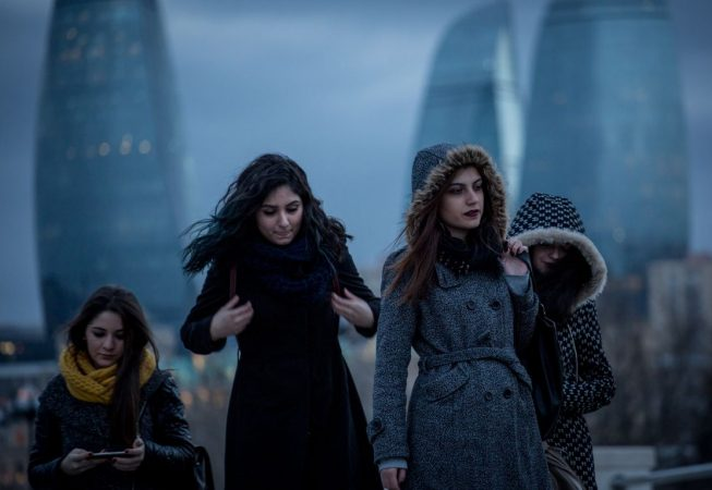 Girls walk on the Caspian Sea embankment in Baku. The distinctive Flame Towers can be seen in the background.