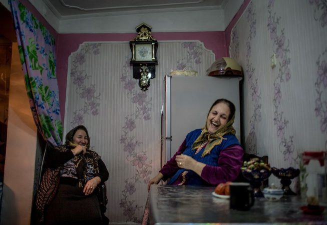 Nina (left) and Jovhar drink tea in a kitchen in the Alatava 2 district