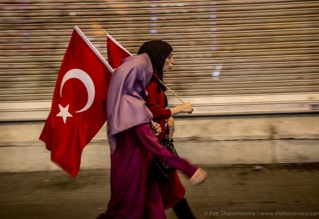 Covered female Erdogan supporters waving Turkish flags as they walk up Istiklal street of Istanbul, Turkey