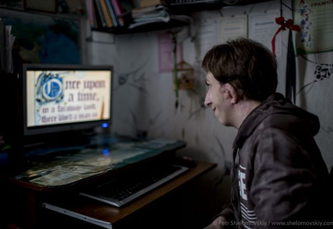 Denis Sviridenko,15, who was born without ears as a result of Chernobyl disaster plays a videogame on his computer