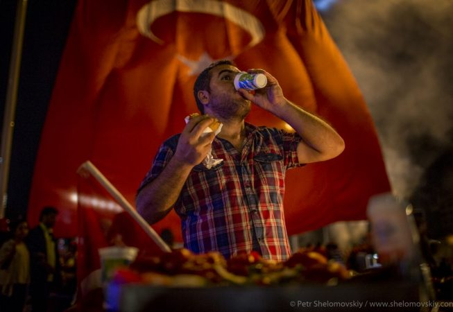 Pro-government supporter refreshes himself with a glass of ayran during the  celebrations of the failed coup attempt in Taksim square of Istanbul, Turkeyin Taksim square of Istanbul, Turkey