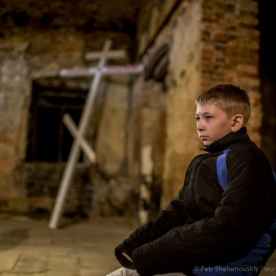 Young boy during Easter mass in destroyed Orthodox church in Petrovskiy district of Donetsk