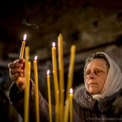 Female believer lighting candles during Easter mass in destroyed Orthodox church in Petrovskiy district of Donetsk