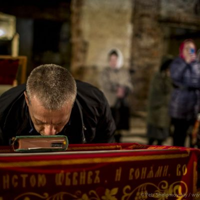 A man kissing the Bible during Easter mass in destroyed Orthodox church in Petrovskiy district of Donetsk