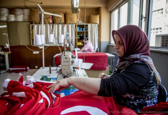 Flag factory worker is busy making another set of Turkish flags. The factory works 24x7 to supply growing demand. Istanbul, Turkey