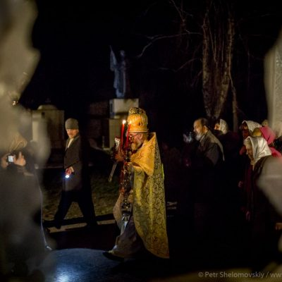 Priests and worshippers during the easter procession as seen through the broken glass window of destroyed church in Petrovskiy district of Donetsk