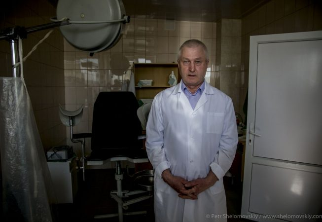 Viktor Khanaev a doctor and a city council member of Novozybkov in western Russia poses for a photograph at his workplace