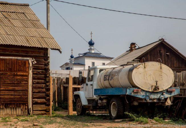 Soviet era water tanker truck is parked behind the church in Khuzhir village in Olkhon island.