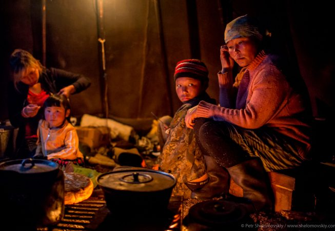 Yadne family members gather around open fire in their chum in the family herding camp on the left  bank of Yenisey river in West Siberia