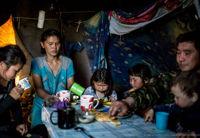 Pavel Yarotskiy, his wife Izolda and their children are having tea in their chum in the family herding camp on the left bank of Yenisey river in West Siberia