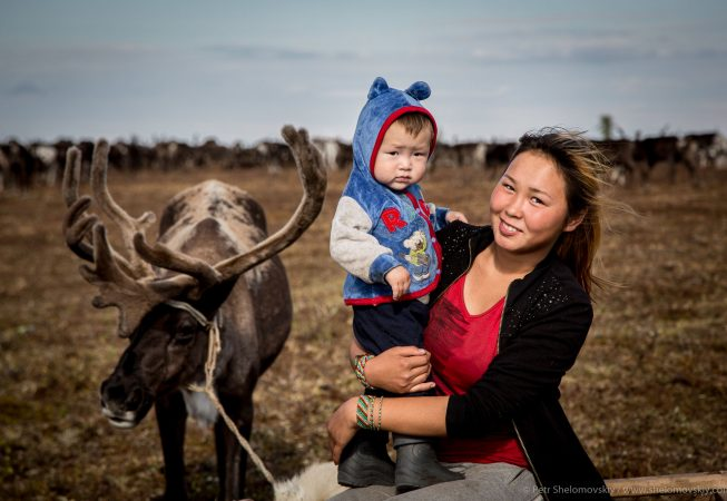 17 yo Nadezhda Yadne is posing for a picture with her 1.5 yo nephew Bogdan in the family herding camp on the left bank of Yenisey river in West Siberia