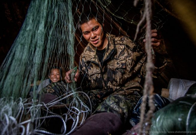 21 yo Nikolay Yadne is preparing fishing net in the family herding camp on the left bank of Yenisey river in West Siberia